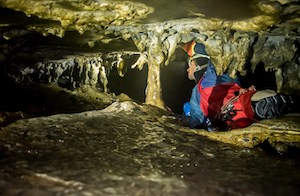 Man caving tight crevices on extreme caving trip
