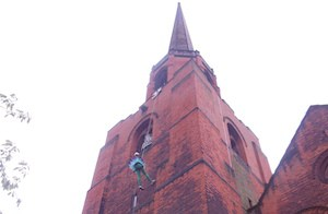 Woman abseiling down church for charity