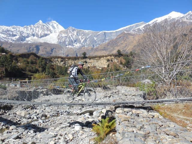 Cycling across Bridge Nepal