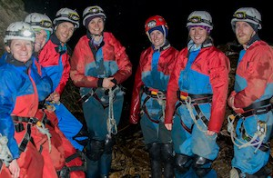 Group of beginner cavers pose in Yorkshire cave