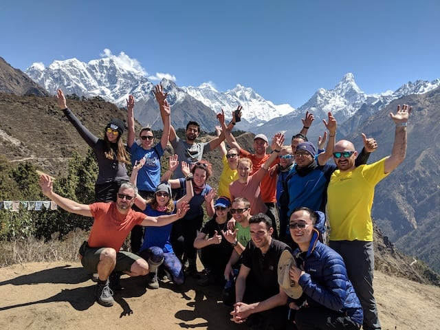 Large charity group posing behind Everest