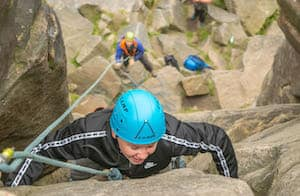Teenager rock climbing in Peak District