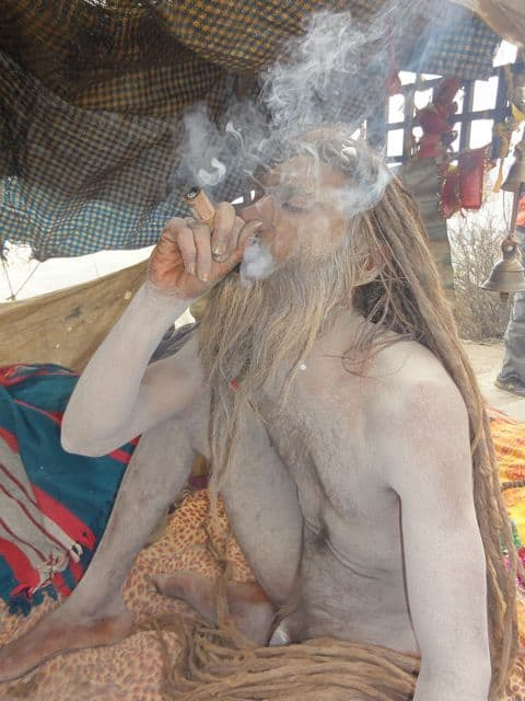 Smoking naked holy man