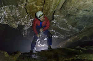 Abseiling into the vertical cave chamber of Giants Hole near Hope in the Peak District