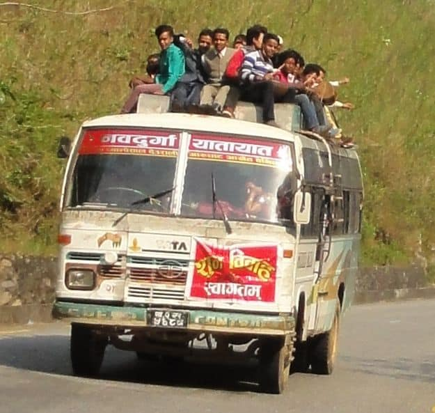 riding on the roof of a bus in Nepal